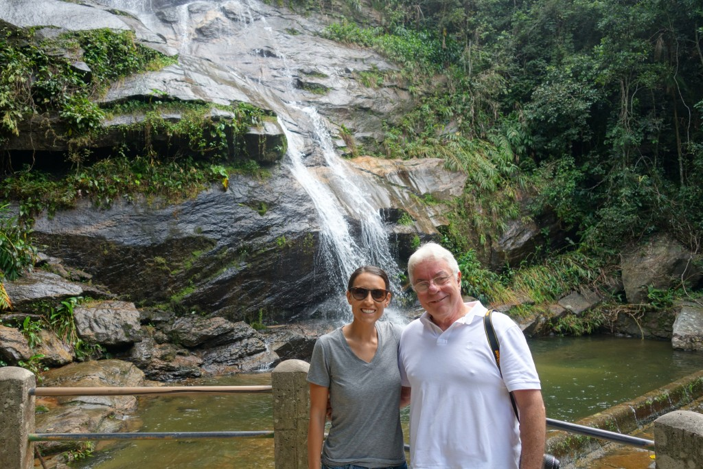 Katie and Celso in front of a waterfall at Tijuca National Park